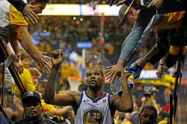 Golden State Warriors' Kevin Durant (35) is congratulated by fans as he exits the court after defeating the San Antonio Spurs during Game 5 of their NBA first-round playoff series at Oracle Arena in Oakland, Calif., on Tuesday, April 24, 2018. The Golden State Warriors defeated the San Antonio Spurs 99-91. (Randy Vazquez/Bay Area News Group)