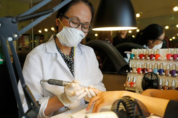 Owner of Leann's Nails Lan Anh Truong works on a customer's nails at her shop in Alameda, Calif., on Friday, April 27, 2018. Leann's Nail is part of the Healthy Nail Salon Collaborative, a program which helps salons switch products and add ventilation systems to improve working conditions. (Laura A. Oda/Bay Area News Group)