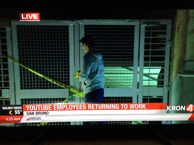 Screenshot of a KRON4 broadcast showing an unidentified worker taking down police tape from an entrance to the patio where Tuesday's shooting at YouTube headquarters occurred.