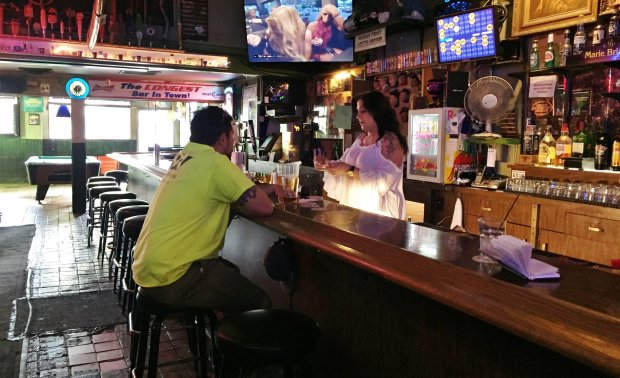"Bartender Debbie Rodriguez serves customer Adrian Vargas Jr. at The Place,a San Jose cocktail lounge that boasts having ""the longest bar in town."" (Sal Pizarro/Bay Area News Group)"
