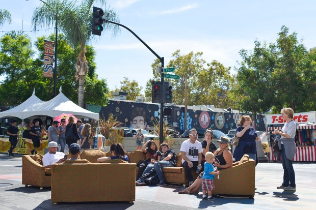 People hang out on sofas during the SoFA Street Fair on South First Street in San Jose, Calif., on Sunday, Sep. 24, 2017. The fair featured food, arts and music. (Photo by Brandon Chew)