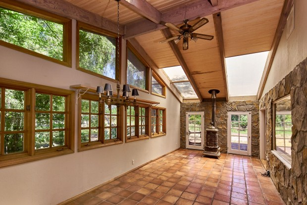 The three-bedroom, two-bathroom ranch-style home includes a front garden-facing sunroom.
