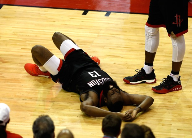 James Harden (13) of the Houston Rockets lies on the court after a possible injury in the first half against the Golden State Warriors in Game One of the Western Conference Finals of the 2018 NBA Playoffs at Toyota Center on May 14, 2018, in Houston, Texas.  (Photo by Bob Levey/Getty Images)