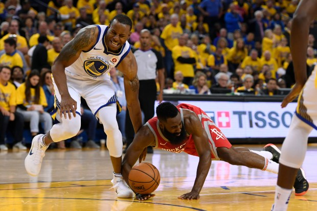Houston Rockets' James Harden (13) lands on the ankle of Golden State Warriors' Andre Iguodala (9) while dribbling the ball during the fourth quarter of Game 3 of the NBA Western Conference finals at Oracle Arena in Oakland, Calif., on Sunday, May 20, 2018. The Golden State Warriors defeated the Houston Rockets 126-85. (Jose Carlos Fajardo/Bay Area News Group)