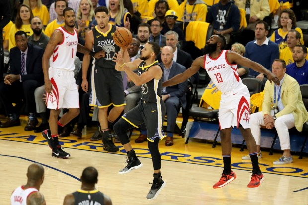 Golden State Warriors' Stephen Curry (30) lays up a shot past Houston Rockets' James Harden (13) during the first quarter of Game 4 of the NBA Western Conference Finals at Oracle Arena in Oakland, Calif., on Tuesday, May 22, 2018. (Ray Chavez/Bay Area News Group)