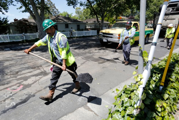 Crews from O'Grady Paving, Inc. contractors with the city of San Jose repair patches on Willow Street west of Lincoln Avenue in the Willow Glen area of San Jose, Calif., on Wednesday, May 30, 2018. There are over $3 billion in transportation projects like this one in the Bay Area alone that were funded the new state gas tax and registration fees -- half of which could be eliminated, deferred or delayed if voters decide to repeal the measure. (Laura A. Oda/Bay Area News Group)