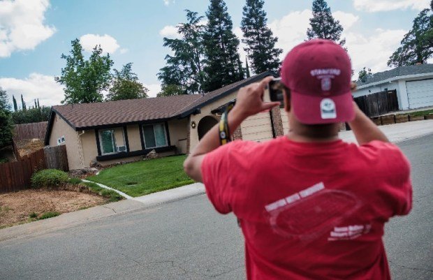 A bystander takes a photo of the home of Joseph James DeAngelo, the suspect in the Golden State Killer crimes. (Nick Otto/For The Washington Post)