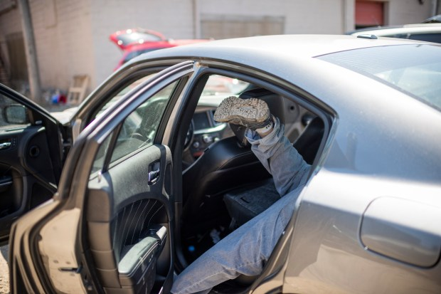 Travis Wolford, 24, cleans personal belongings out of a newly repossessed car at Relentless Recovery's lot in April. Must credit: Photo by Dustin Franz for The Washington Post