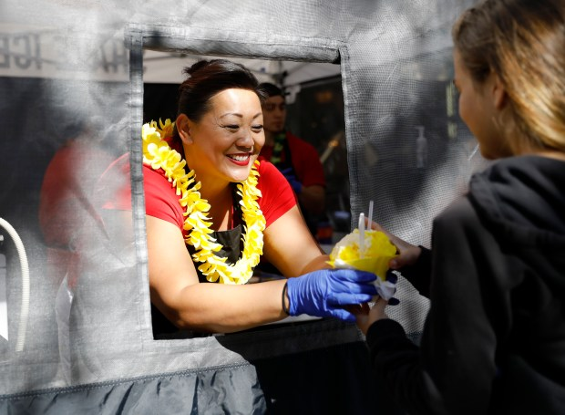 Vivian Brandt, owner, hands a shave ice to a young customer at Auntie Viv's Shave Ice at the farmers market in Santana Row in San Jose, Calif., on Wednesday, May 30, 2018. (Nhat V. Meyer/Bay Area News Group)