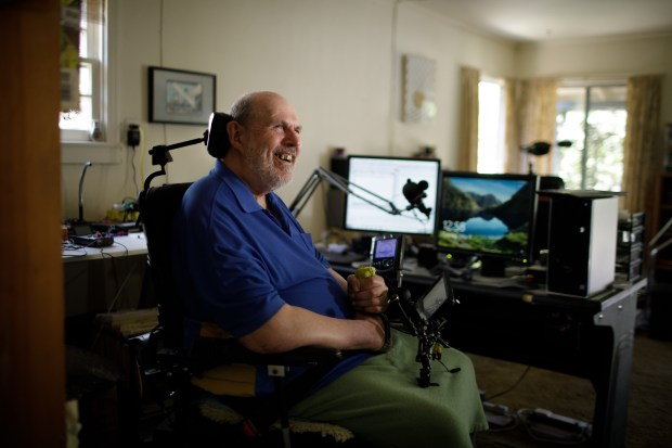 Portrait: A Menlo Park resident Joe Karnicky, who is wheelchair-bound due to multiple sclerosis, lives with a co-housing roommate, so Karnicky could rely on the roommate for help around the house. In the background is a computer set up he uses for speech controlled computing to control functionalities such as opening the door, making phone calls and various everyday tasks. (Dai Sugano/Bay Area News Group)