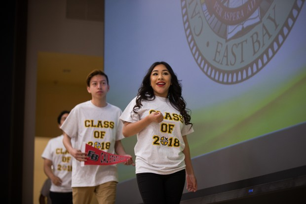 Graduating senior Coraima Bolanos Alejo, 17, of San Jose walks on the stage during a school event, where college-bound seniors announced their university or college choice in front of their family members and fellow students, on May 18, 2018, at Cristo Rey San Jose Jesuit High School. Bolaos Alejo will attend California State University, East Bay in the fall. (Dai Sugano/Bay Area News Group)