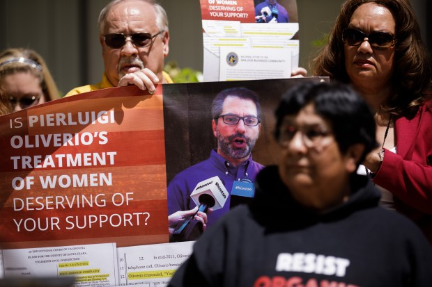 Supporters of the Santa Clara County Democratic Central Committee's resolution condemning former San Jose City Council member Pierluigi Oliverio's alleged sexual harassment and verbal abuse while he was a sitting council member, hold a banner during a press conference on May 4, 2018, in front of the Santa Clara County administrative building in San Jose. (Dai Sugano/Bay Area News Group)