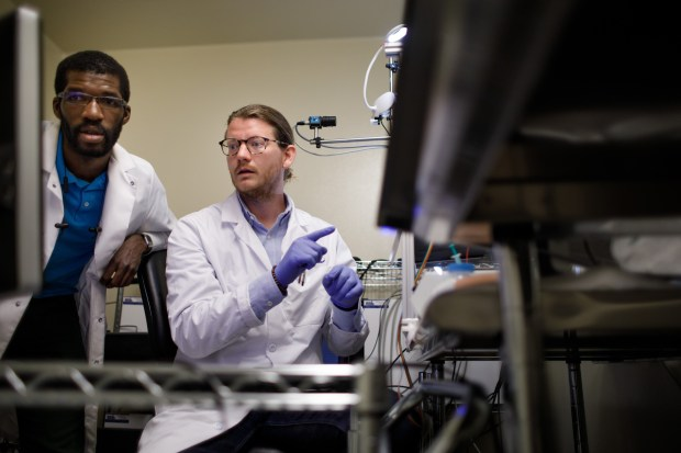 Gregory Corder, center, a postdoctoral fellow in anesthesiology and Biafra Ahanonu, a Ph.D. candidate in cell biology, both at Stanford University, talk about an experiment on neural mechanisms of pain on May 30, 2018 in a Stanford University's research facility in Palo Alto. (Dai Sugano/Bay Area News Group)