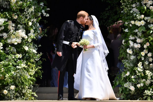 WINDSOR, UNITED KINGDOM - MAY 19: Britain's Prince Harry, Duke of Sussex kisses his wife Meghan, Duchess of Sussex as they leave from the West Door of St George's Chapel, Windsor Castle, in Windsor on May 19, 2018 in Windsor, England. (Photo by Ben STANSALL - WPA Pool/Getty Images)