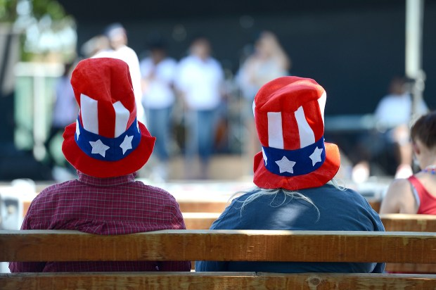 A couple in Uncle Sam hats listen to the live entertainment at Antioch's annual Fourth of July parade and festival in Antioch, Calif., on Saturday, July 4, 2015. The parade circled downtown Antioch followed by the event at the Contra Costa County Fairgrounds that featured live music, food, fun for the kids and culminating in a fireworks show. (Dan Honda/Bay Area News Group archive)