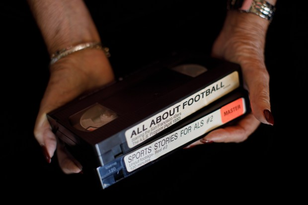 Portrait: Producer Julia Hutton of Hawaii holds on May 21, 2018, two of the VHS cassette tapes featuring oral histories recorded in 1990 of former 49ers, such as Y.A. Tittle, for an ALS fundraising project that has been resurrected. (Dai Sugano/Bay Area News Group)