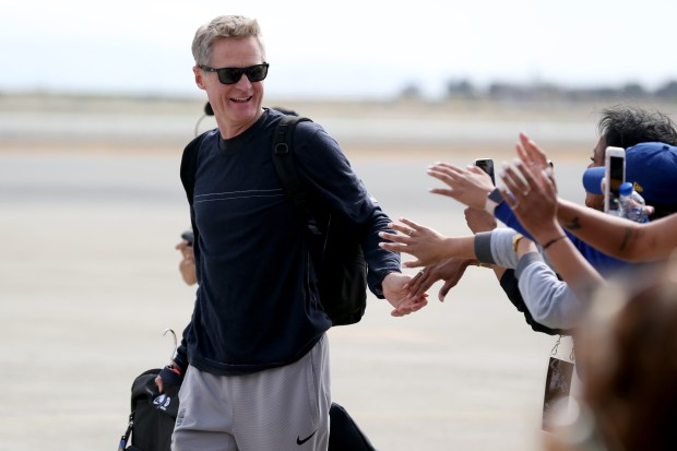 After completing a four-game sweep of the Cleveland Cavaliers to win the 2018 NBA Championship, Golden State Warriors coach Steve Kerr celebrates with team employees as the team arrives back in Oakland, Calif., on Saturday, June 9, 2018. (Anda Chu/Bay Area News Group)