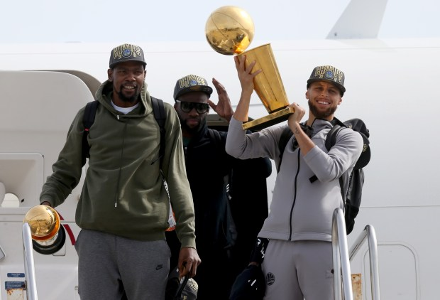 After completing a four-game sweep of the Cleveland Cavaliers to win the 2018 NBA Championship, Golden State Warriors' Kevin Durant, Draymond Green and Stephen Curry exit their plane as they arrive back in Oakland, Calif., on Saturday, June 9, 2018. (Anda Chu/Bay Area News Group)