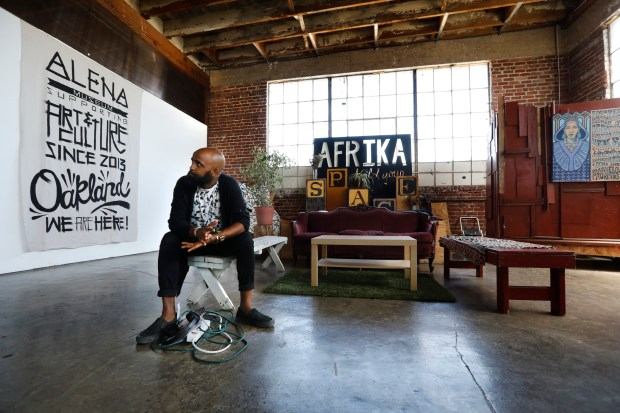 Hager Asefaha, known in the artist community as Seven, takes a break from setting up the art space for an event at the Alena Museum in Oakland, Calif., on Friday, June 15, 2018. The Alena Museum, an art gallery dedicated to supporting work that reflects on the African diaspora, is fighting to keep its space in fast-gentrifying West Oakland. (Laura A. Oda/Bay Area News Group)