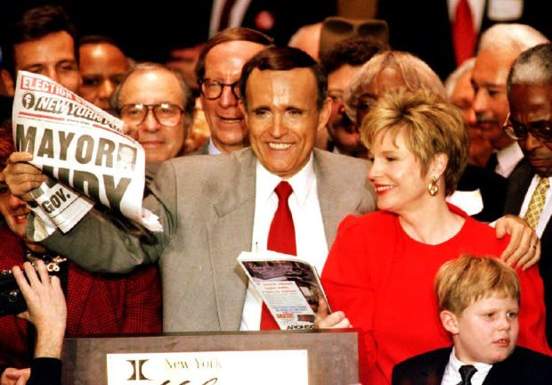 NEW YORK, NY - NOVEMBER 3: Mayor-elect Rudolph Giuliani holds up 03 November 1993 a newspaper proclaiming him the mayor of New York after winning the tight race against Democratic incumbent David Dinkins. With Giuliani are his wife Donna (2ndR) and his son Andrew (R). Giuliani is the first Republican elected mayor since 1965. (Photo credit should read HAI DO/AFP/Getty Images)