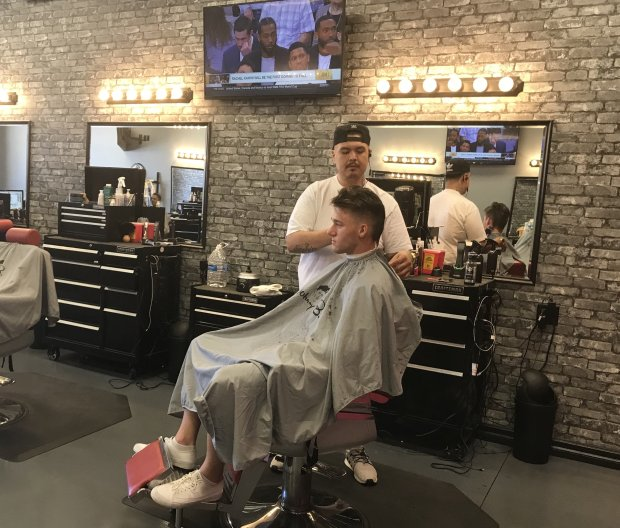Abraham Herrera, 28, cuts Caiden Matheny's hair at a barbershop in Mennifee, Ca., and discuss the initiative to split California into three states. (Bay Area News Group/Julia Prodis Sulek)
