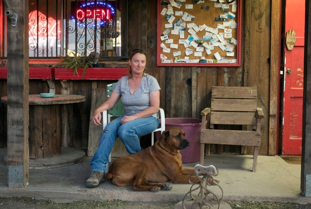 Owner Kim Lippert, 51, of Panoche, poses for a portrait with her customer's dog Nitro, in front of the Panoche Inn, in Panoche (San Benito County), California on Wednesday, June 13, 2018. The Inn lies near the border of the proposed three Californias: Northern California (Merced County), California (San Benito County), and Southern California (Fresno County) (LiPo Ching/Bay Area News Group)