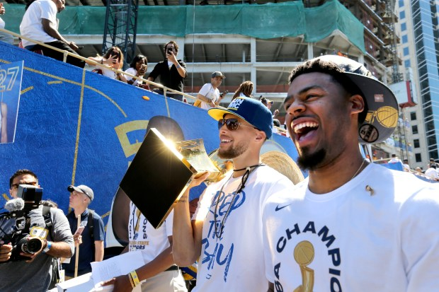 Golden State Warriors' Stephen Curry carries the Larry O'Brien NBA Championship Trophy along with Quinn Cook as they walk towards their double decker to start the Warriors championship parade in downtown Oakland, Calif., on Tuesday, June 12, 2018. (Ray Chavez/Bay Area News Group)
