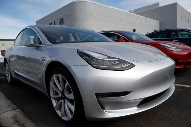 In this April 15, 2018, file photo unsold 2018 Model 3 Long Range versions sit on a Tesla dealer's lot in the south Denver suburb of Littleton, Colo. (AP Photo/David Zalubowski, File)