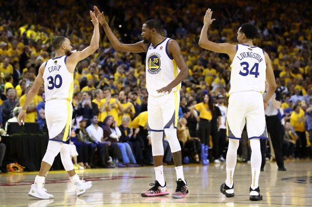 Stephen Curry (30) of the Golden State Warriors celebrates with Kevin Durant (35) and Shaun Livingston (34) against the Cleveland Cavaliers in overtime during Game 1 of the 2018 NBA Finals at ORACLE Arena on May 31, 2018 in Oakland, California. (Photo by Ezra Shaw/Getty Images)