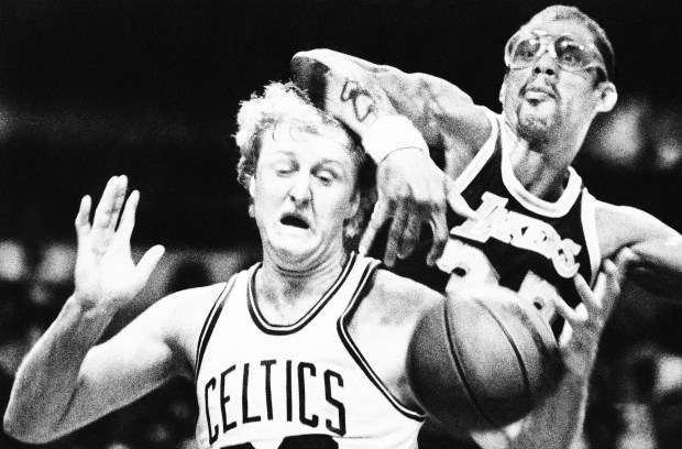 Larry Bird of the Boston Celtics, left, reacts as he is blocked by Kareem Abdul-Jabbar of the Los Angeles Lakers, right, in the second game of the NBA championship series at the Boston Garden Thursday, June 1, 1984 in Boston. Boston defeated Los Angeles in overtime, 124-121, to even the series at one game. (AP Photo/Peter Southwick)