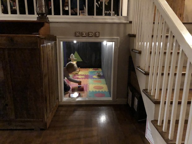 an adorable little playroom is tucked under the stairs at pico