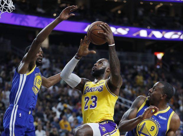 Los Angeles Lakers forward LeBron James (23) shoots between Golden State  Warriors forward Kevin Durant cf65d9c3a