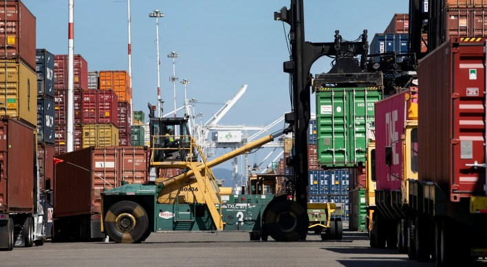 OAKLAND, CA. - July 15: A longshoreman stacks cargo containers for loading onto ships at the Port of Oakland, Thursday, July 15, 2021. (Karl Mondon/Bay Area News Group)