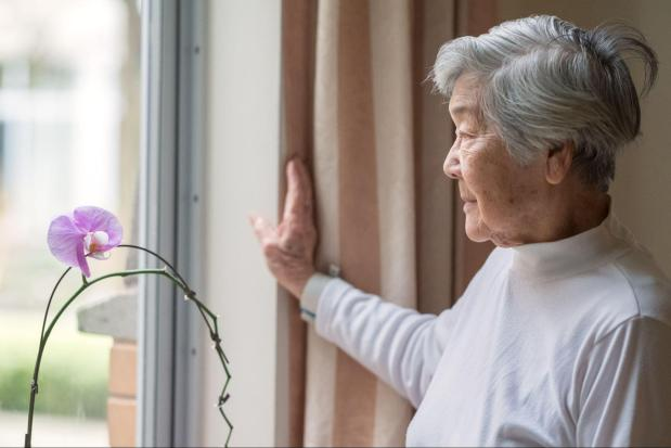 Senior woman looking out a window.
