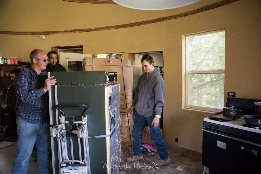 """a tall, handsome, extremely young-looking guy handles a dolly while his bright n' sprightly son looks on and smiles. In the kitchen of the """"yurt"""", rough inside"""