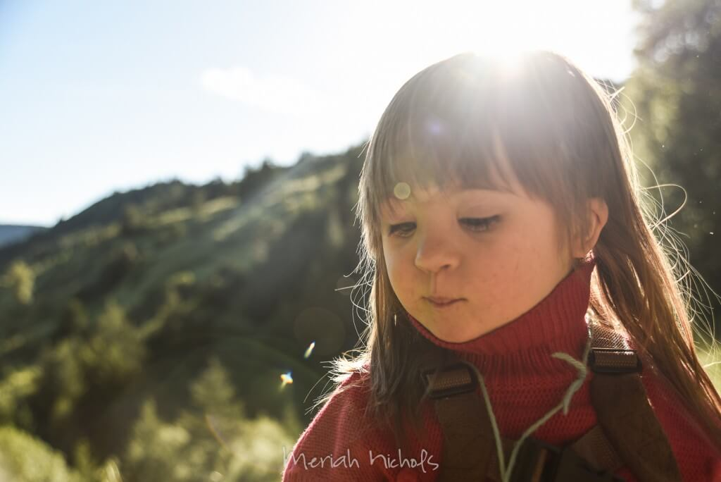 young girl with red sweater looks down - behind her are mountains