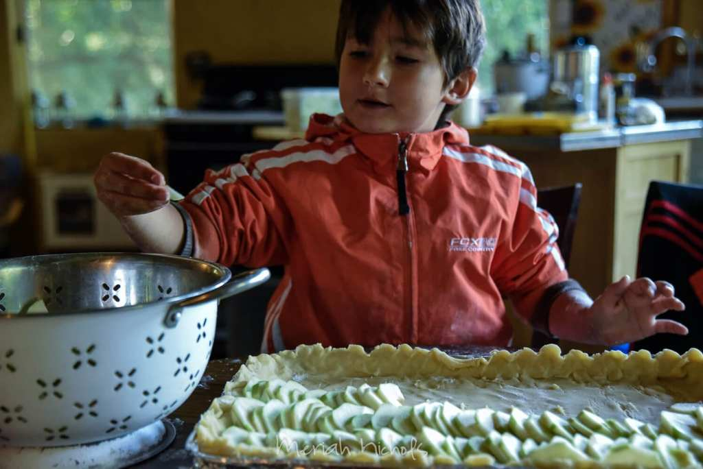 small boy reaches for sliced apples and arranges the slices on the tray in front of him