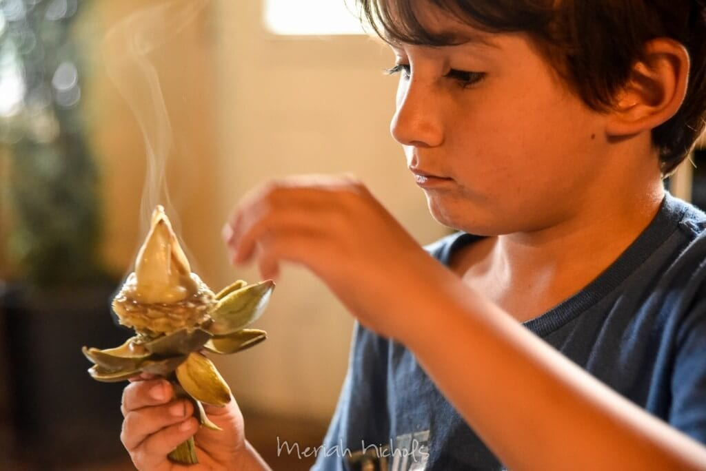 small boy holding up an artichoke that is steaming