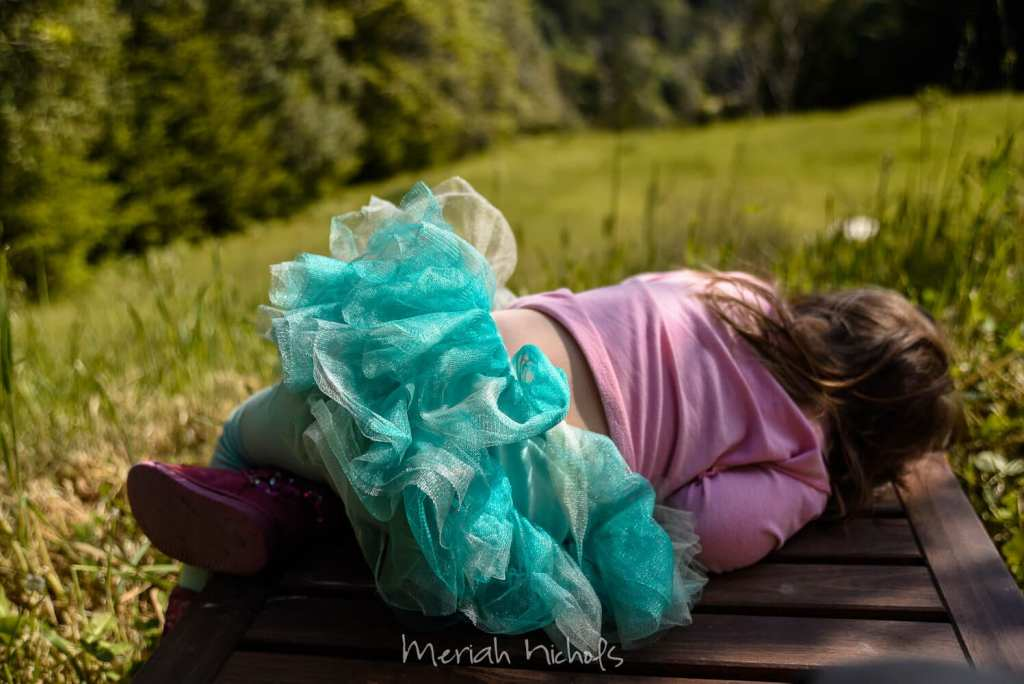 girl half lying down, back facing camera. she is wearing a blue tutu