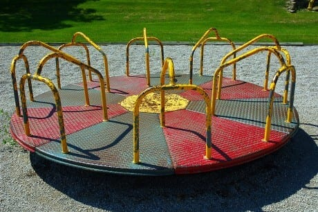 a children's merry go round - in green and red , with a yellow circle center