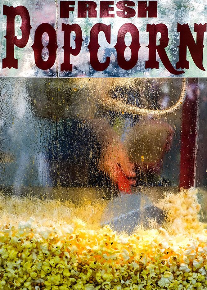 Gillar den diffusa mänskliga närvaron med handen som skottar popcorn.