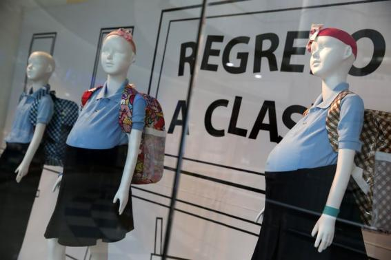 Mannequins of pregnant schoolgirls are seen in a shop window at a shopping mall in Caracas