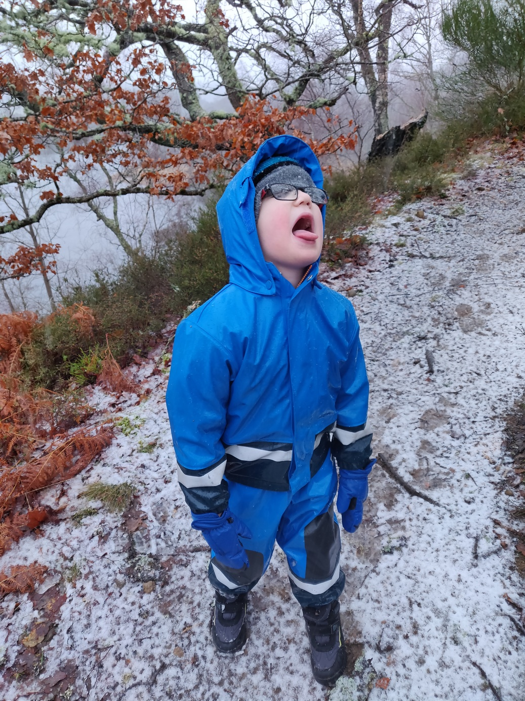 child in snow with tongue sticking out