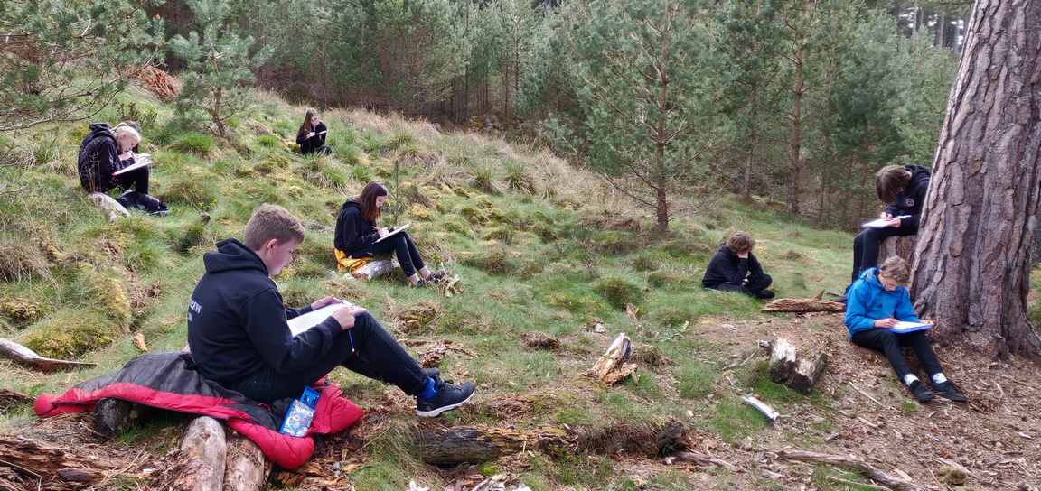School pupils doing creative writing activity in woodland