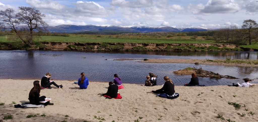 Pupils on beach beside River Spey
