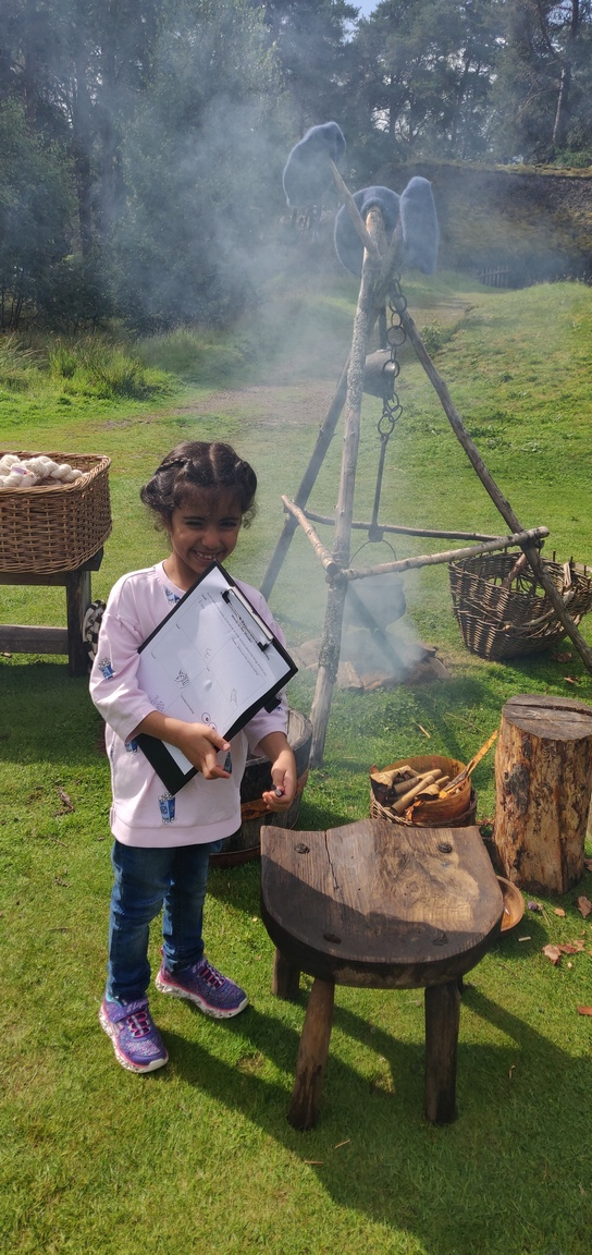 Young girl with clipboard beside a fire pit