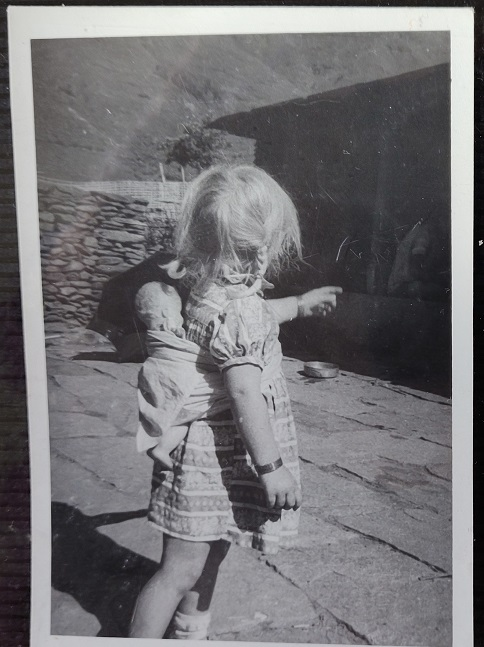 Little girl with doll strapped to her back