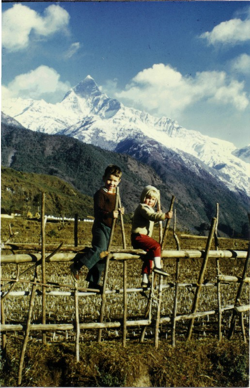 Children on a bamboo fence in front of mountains in Nepal