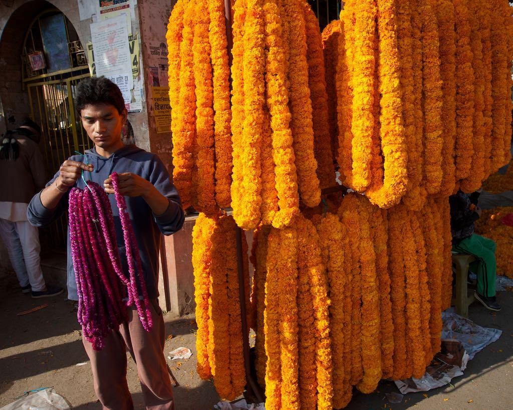 A street stall of marigold garlands by Rowan Butler