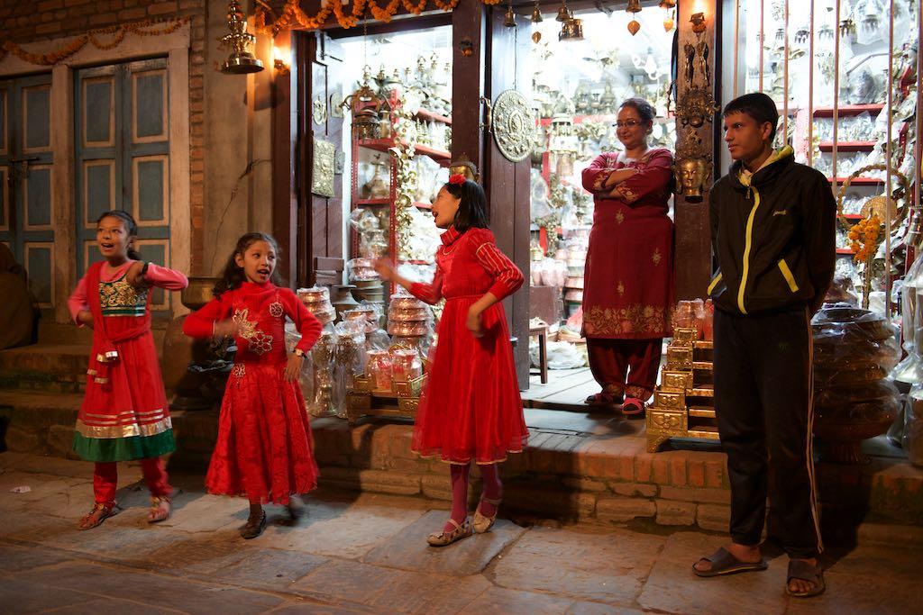 Girls singing outside shop for Tihar in Kathmandu by Rowan Butler
